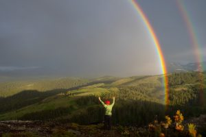 A rainbow arches over the Badger Two Medicine, early July 2020